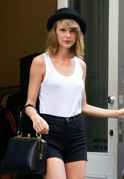 celebrity Taylor Swift donning a black bowler hat